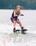 男孩滑雪微笑的窍门年轻人 免版税库存图片