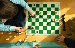 男孩演奏年轻人的棋楼层 免版税图库摄影