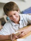男孩演奏年轻人的MP3播放器 免版税库存照片
