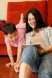 男孩演奏片剂的比赛母亲 免版税库存图片