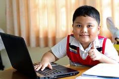 男孩演奏笔记本。 免版税库存图片