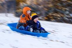 男孩激动的乘驾雪撬 图库摄影