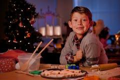 男孩烘烤圣诞节曲奇饼 免版税图库摄影