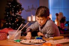 男孩烘烤圣诞节曲奇饼 库存照片