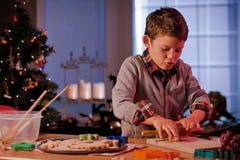 男孩烘烤圣诞节曲奇饼 免版税库存图片