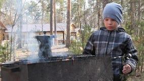 男孩烹调在火的食物在格栅 国家休息 股票录像