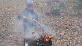 男孩烹调在火的食物在格栅 国家休息 影视素材