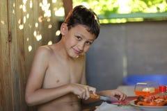 年轻男孩烹调 图库摄影
