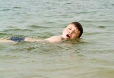 男孩爬行游泳 免版税库存照片