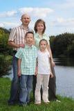 男孩父亲在池塘坚持附近的女孩母亲 免版税库存照片