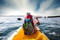 年轻男孩犁通过海的水有他的独木舟的 免版税图库摄影