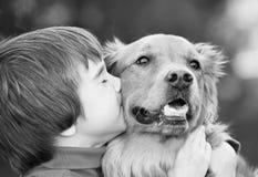 男孩狗亲吻 免版税库存图片