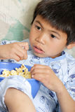男孩玉米花snacking的年轻人 免版税图库摄影