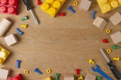 男孩玩具框架背景 戏弄工具、建筑块和立方体在木桌上 顶视图 平的位置 免版税图库摄影