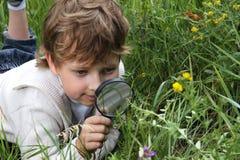 男孩玻璃扩大化 免版税库存照片