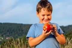 男孩用一个红色苹果 免版税库存图片