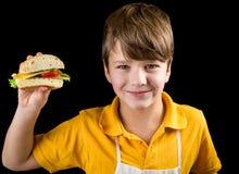 男孩用三明治在手中 免版税库存图片