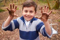 男孩用使用在森林里的泥泞的手 库存照片