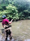 男孩用假蝇钓鱼在河 免版税库存照片
