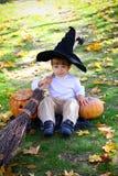 男孩用南瓜、笤帚和帽子 图库摄影