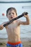 男孩用在海滩的棍子 免版税库存照片