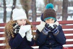 男孩用女孩一起饮料咖啡在长凳的冬天 免版税库存照片