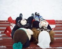 男孩用女孩一起饮料咖啡在长凳的冬天 图库摄影