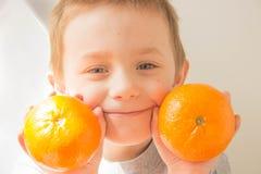 男孩用桔子在他的手上 免版税库存照片