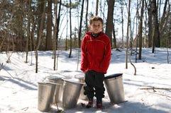 男孩用桶提前面少许树汁多雪的春天 免版税库存照片