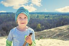 男孩用棍子在自然走 免版税库存照片