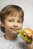 男孩用汉堡 库存照片
