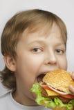 男孩用汉堡 库存图片