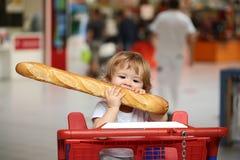 男孩用法国面包 免版税库存照片