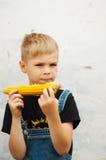 年轻男孩用玉米棒子在后院 男孩愉快的ab 免版税库存照片