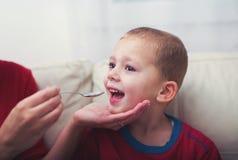 男孩用症状手,采取糖浆的口蹄疫 免版税库存照片