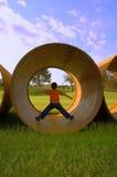男孩用管道输送地下 免版税图库摄影