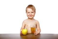 男孩用苹果汁 库存照片