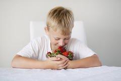 男孩用草莓 库存照片