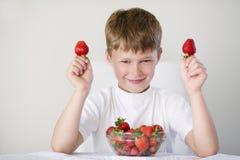 男孩用草莓 免版税库存图片