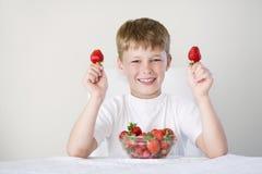 男孩用草莓 免版税库存照片