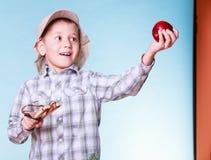 年轻男孩用途后摆投球法举行苹果 免版税库存图片