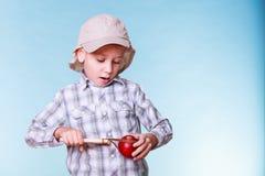 年轻男孩用途后摆投球法举行苹果 免版税库存照片