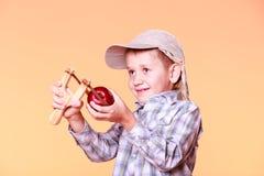 年轻男孩用途后摆投球法射击苹果 免版税库存照片