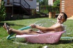 男孩用飞溅水在热的夏日 免版税库存图片
