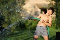 男孩用飞溅水在热的夏日 免版税库存照片