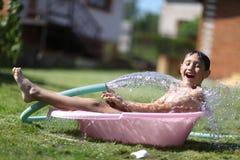 男孩用飞溅水在热的夏日 库存照片