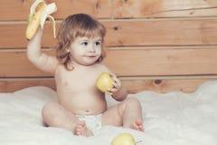 男孩用香蕉和苹果 免版税库存照片