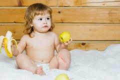 男孩用香蕉和苹果 图库摄影