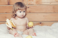 男孩用香蕉和苹果 免版税图库摄影