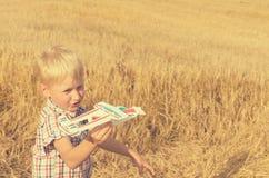 男孩用他的手跑飞机的模型入天空 免版税库存照片